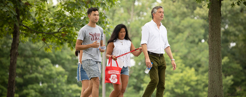 Family walking across campus with their Cornell student