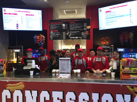 Group of concessions employees standing behind the service counter with menus above them.