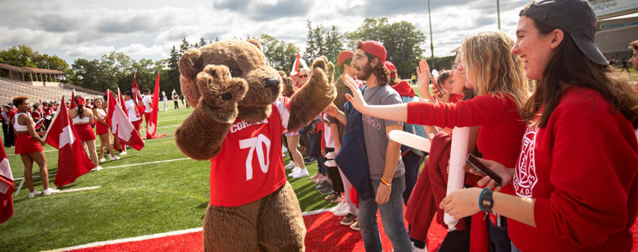 Students high five Touchdown mascot at Homecoming parade on football field