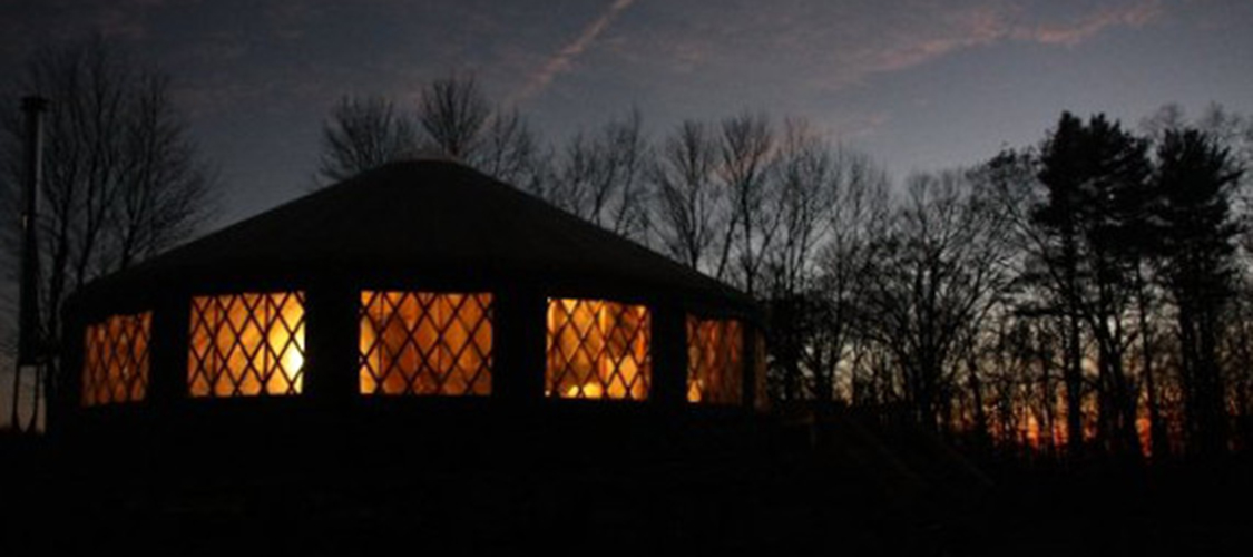 A yurt on the chalenge course is lit by the fire within