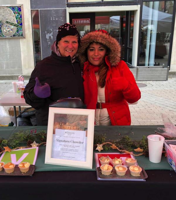 Two people bundled up in warm coats at a chowder event booth