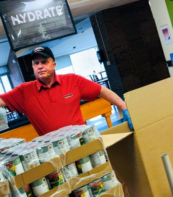 Tommy LaLonde, a cook at Robert Purcell Marketplace Eatery, boxes up food donations.