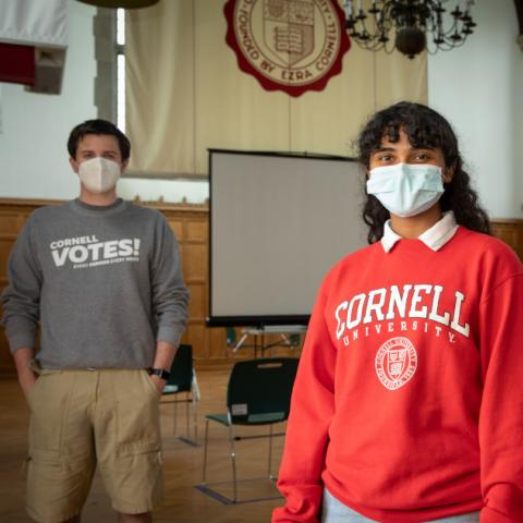 Three students from Cornell Votes stand in Willard Straight Hall Memorial Room